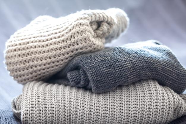 Bellissimi abiti lavorati a maglia, ordinatamente piegati, primo piano, maglioni fatti a mano.