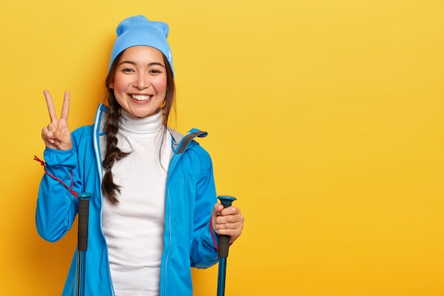 Beautiful korean girl enjoys hiking, poses with trekking sticks, makes peace gesture, wears blue hat and jacket, isolated over yellow background, blank space