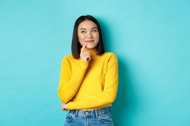 Красивая корейская девушка думает, воображает и улыбается, смотрит в левый верхний угол и мечтает, стоя на синем фоне