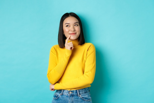 Beautiful korean girl thinking, imaging and smiling, looking at upper left corner and daydreaming, standing against blue background