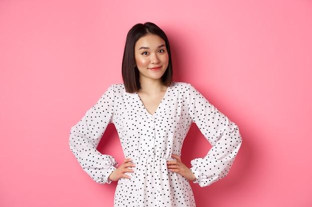 カメラを見て、笑顔、何かを待っている、ピンクの背景に立っているドレスを着た美しい韓国人女性。
