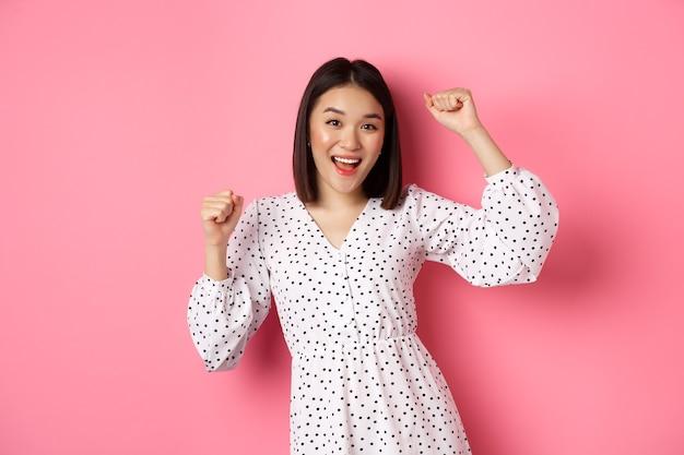 Beautiful korean woman dancing and having fun, smiling happy at camera, posing against pink.