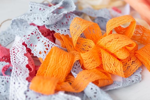 美しいレースのリボンが針子のテーブルの上にあり、ユニークな女性用と子供用のドレスを作成します。