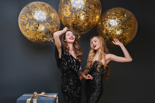 Beautiful ladies dancing with hands up in front of shining helium balloons and smiling. indoor photo of refined brown-haired birthday girl chilling with friend and laughing.