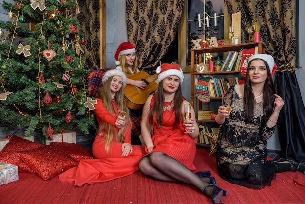 크리스마스 트리 근처에 앉아 샴페인 glases와 아름다운 숙녀