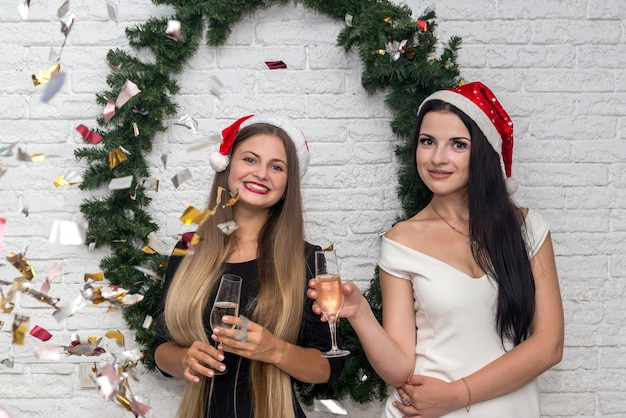 Beautiful ladies with champagne and santa hats