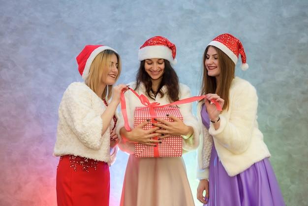 ファッションのイブニングドレスとサンタの帽子のギフトボックスを持つ美しい女性