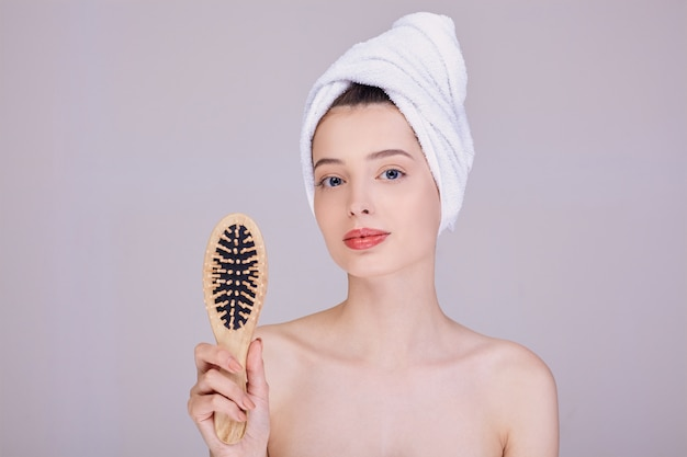 Beautiful lady after a shower holds a wooden comb in her hands.