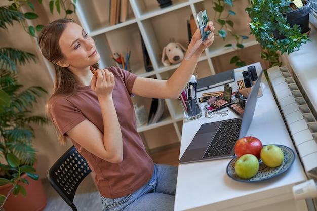 オンラインメイクチュートリアル中に口紅を塗る美しい女性