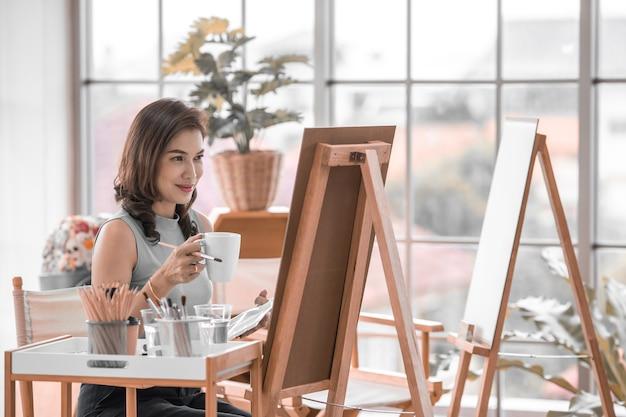 座ってコーヒーマグカップを保持し、部屋の写真を痛めるためにブラシを使用してカジュアルな服を着た美しい女性アジア人女性。自宅での趣味、リラクゼーション、アーティストの仕事のアイデア。