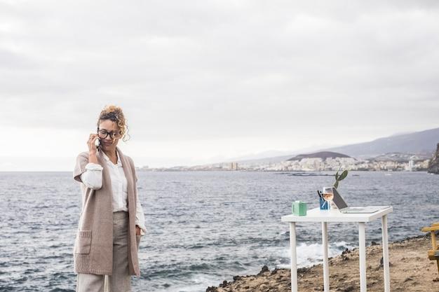 Красивая дама за работой с мобильным телефоном и ноутбуком на рабочем столе в альтернативном офисе на открытом воздухе на берегу океана