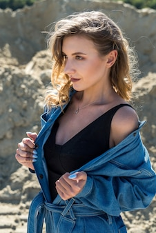 Beautiful lady in blue overalls walks in a sand quarry, active way