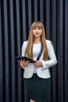 Beautiful lady in business suit holding tablet and posing on abstract background Premium Photo