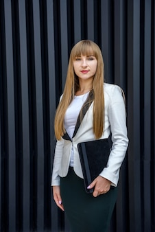 Beautiful lady in business suit holding tablet and posing on abstract background