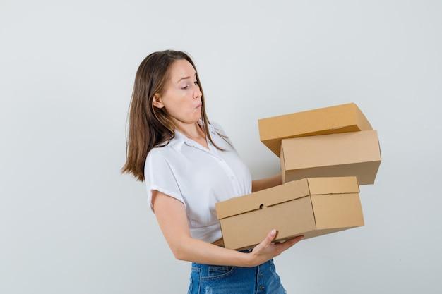 白いブラウスで箱を運んで、問題を抱えているように見える、正面図の美しい女性。