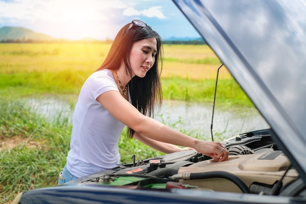 Beautiful lady checking her broken car near the road during her travel on vacation.