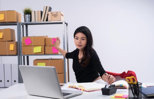 ラップトップから注文をチェックし、棚の上の郵便ポストを拾うために手を伸ばす美しい女性..梱包、eコマース、ビジネスウーマンの準備