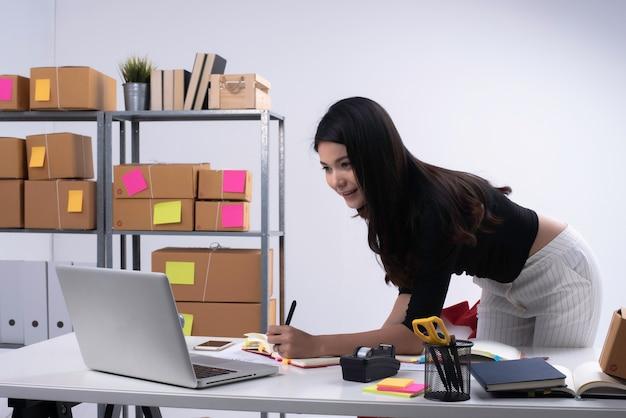 ノートパソコンから注文をチェックし、本に書く美しい女性。梱包、eコマース、ビジネスウーマンの準備をする