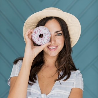 Beautiful lady covering her eye with a donut
