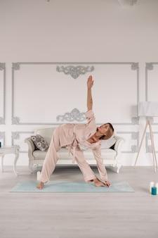 그녀의 아파트에서 쉬고 있는 동안 운동을 하고 연꽃 위치에 앉아 있는 아름다운 여성. 건강 및 라이프 스타일 개념