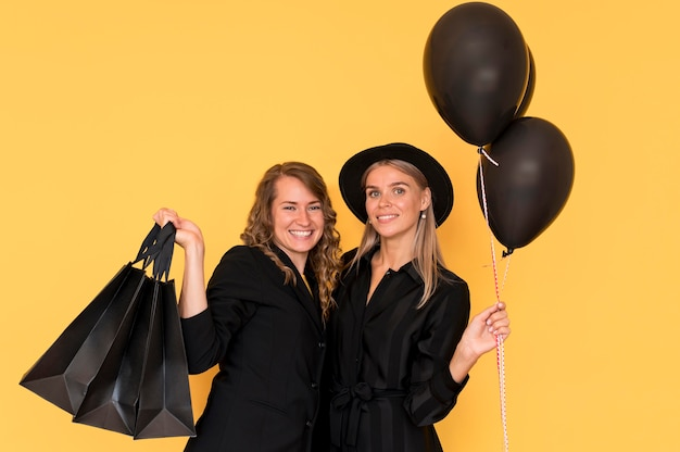 Красивые дамы друзья держат хозяйственные сумки и воздушные шары