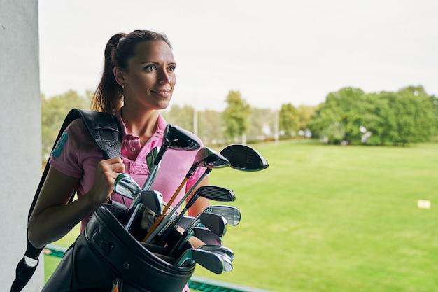 Красивая девушка-гольфистка с мечтательной улыбкой смотрит вдаль