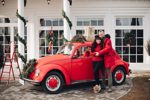 Beautiful lady and her boyfriend hugging by a red car parked near a house with christmas decorations