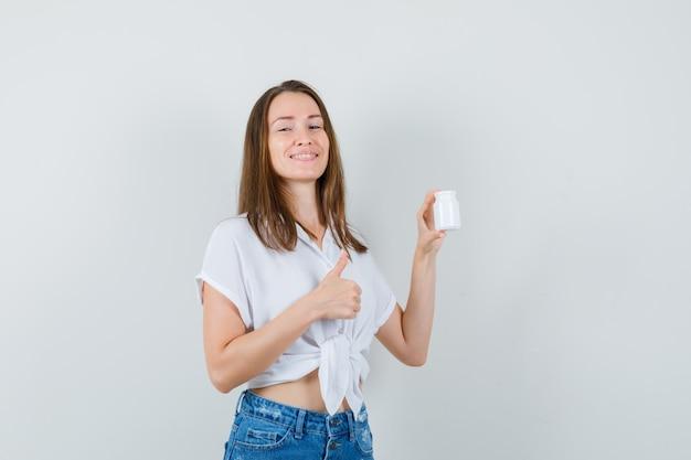 Bella signora che tiene una bottiglia di pillole mentre mostra il pollice in su in camicetta bianca, jeans e sembra allegro, vista frontale.