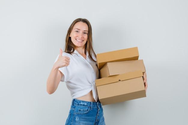 白いブラウスで親指を表示し、満足しているように見える間、ボックスを保持している美しい女性、正面図。