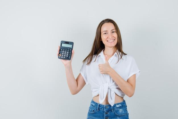 白いブラウス、ジーンズの正面図で親指を表示しながら電卓を保持している美しい女性。