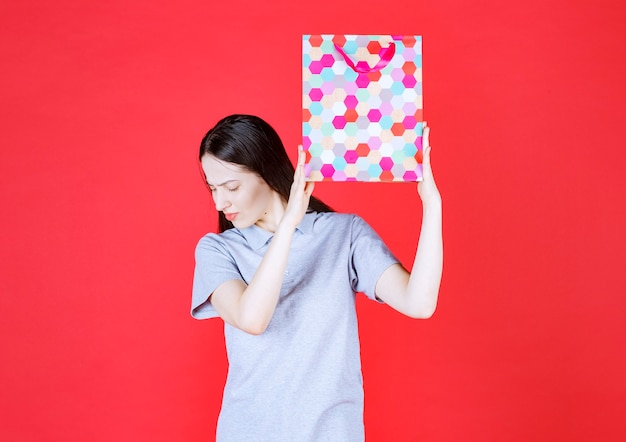 Beautiful lady holding colorful shopping bag and looking down