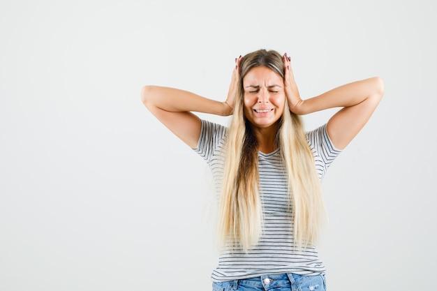 Tシャツを着て耳に手をつないでストレスを感じている美しい女性。正面図。