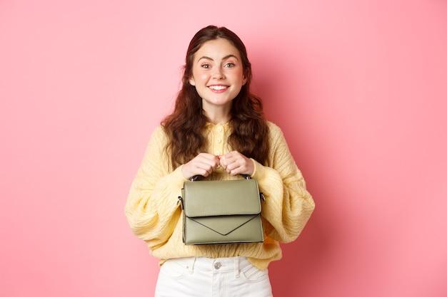 Красивая дама, держащая сумочку в руках возле груди, улыбаясь и возбужденно глядя в камеру, ждет чего-то с искушением, стоя у розовой стены