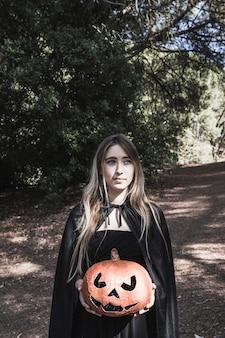 Beautiful lady holding pumpkin in park