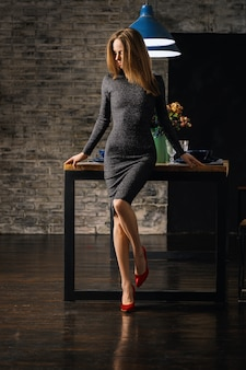 Beautiful lady ib dress leaning on the table with bent knee in red patent leather shoes looking to the floor