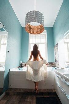 Красивая дама в халате возле ванны с обнаженными плечами