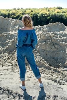 파란색 바지를 입은 아름다운 여인이 모래 채석장에서 적극적으로 산책합니다.