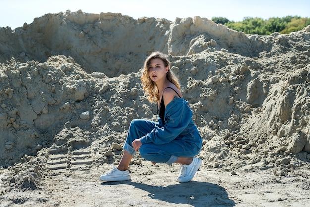 파란 바지에 아름다운 아가씨가 모래 채석장에서 산책