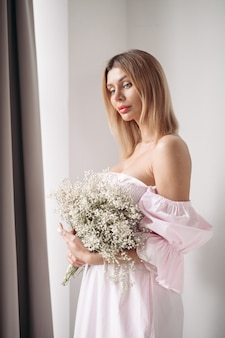 自宅のリビングルームでそれを見ながら花の花束を保持しているドレスの美しい女性。ロマンチックなコンセプト。ライフスタイルのコンセプト