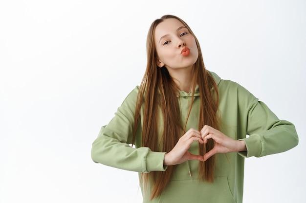 パーカーのキスとハートのサインを示す美しい女性、私はあなたのジェスチャーを愛し、白い背景に対してロマンチックでかわいい立って、緑のパーカーを着ています。