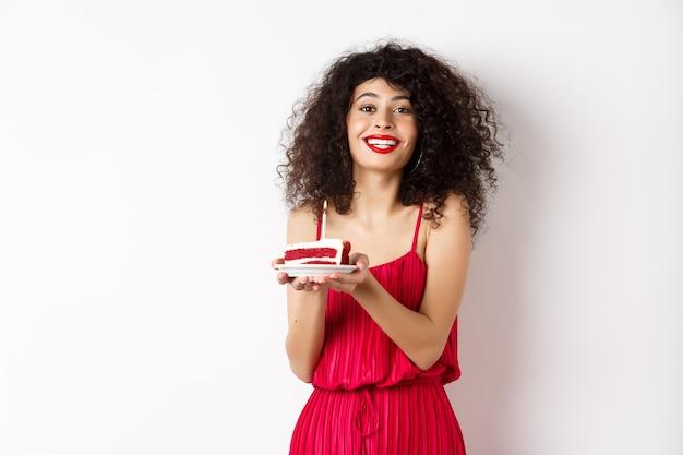 誕生日を祝って、キャンドルでケーキを持って、笑顔で、白い背景の上に幸せに立って、赤いドレスを着た美しい女性。