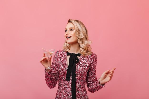 ピンクの壁にマティーニグラスを保持している光沢のあるトップの美しい女性