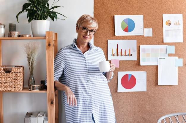 Красивая дама в полосатом наряде позирует с чашкой чая в офисе
