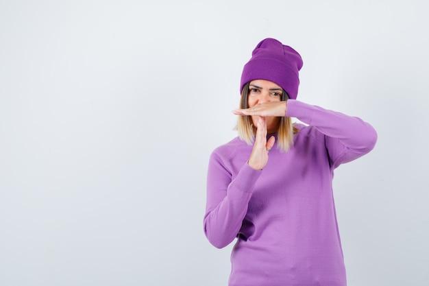 タイムアウトジェスチャーを示し、疲れているように見えるセーターの美しい女性、正面図。
