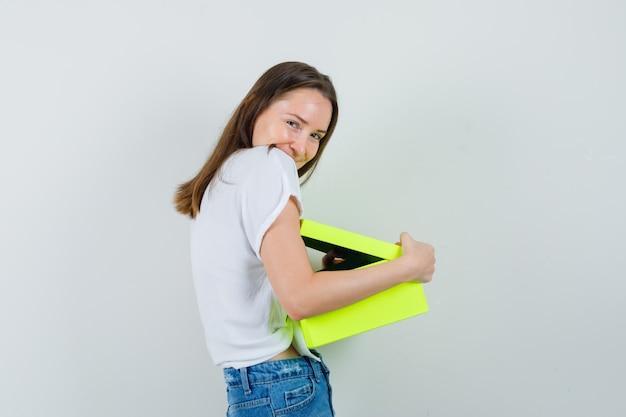 白いブラウスを抱きしめるギフトボックスと陽気に見える、正面の美しい女性。