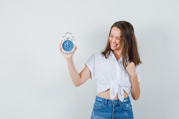 白いブラウスの美しい女性が時計を見て、陽気に見える、正面図。
