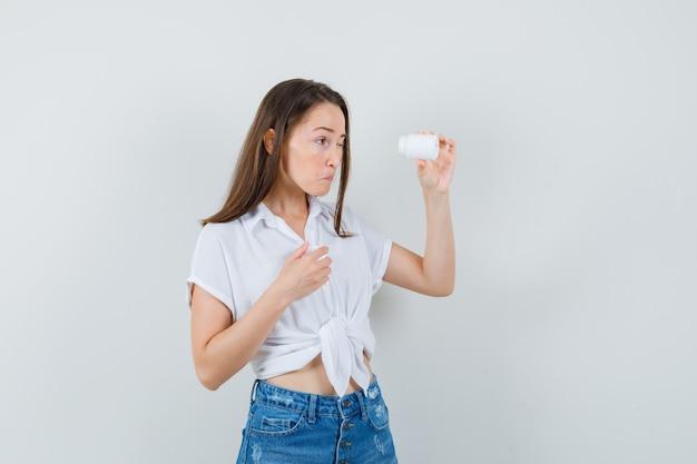 흰색 블라우스에 아름 다운 아가씨 알 약의 병 내부보고 집중, 전면보기.