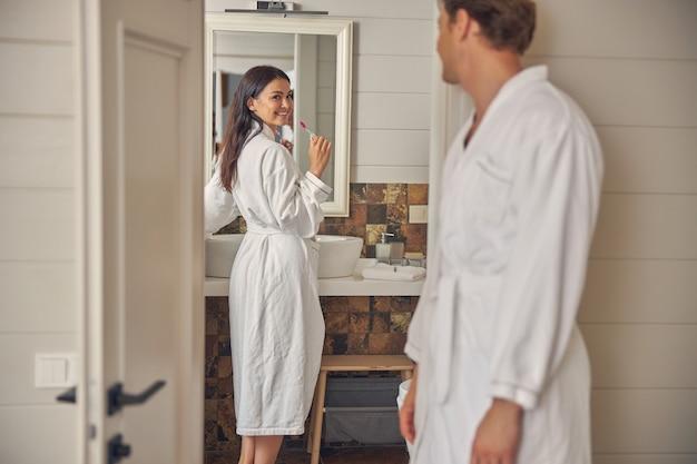 흰색 부드러운 목욕 가운에 아름다운 아가씨는 화장실에 서있는 동안 그녀의 남자 친구를 찾고