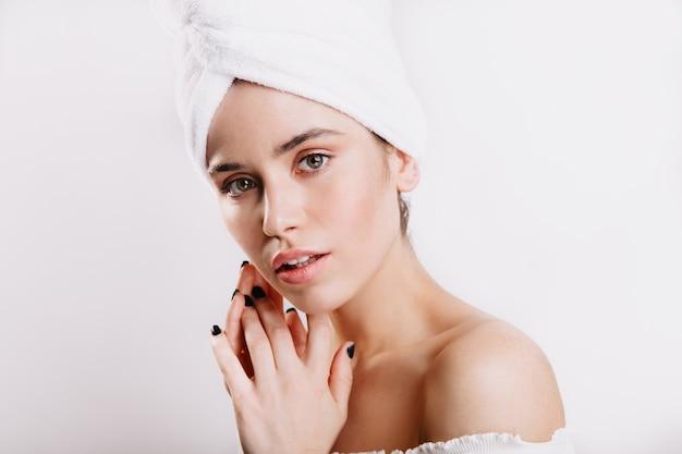 아름다운 아가씨는 부드럽게 흰 벽에 있습니다. 깨끗하고 건강한 피부가 수건으로 포즈를 취하는 젊은 모델.