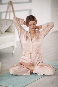 Красивая дама медитирует на полу в своей спальне